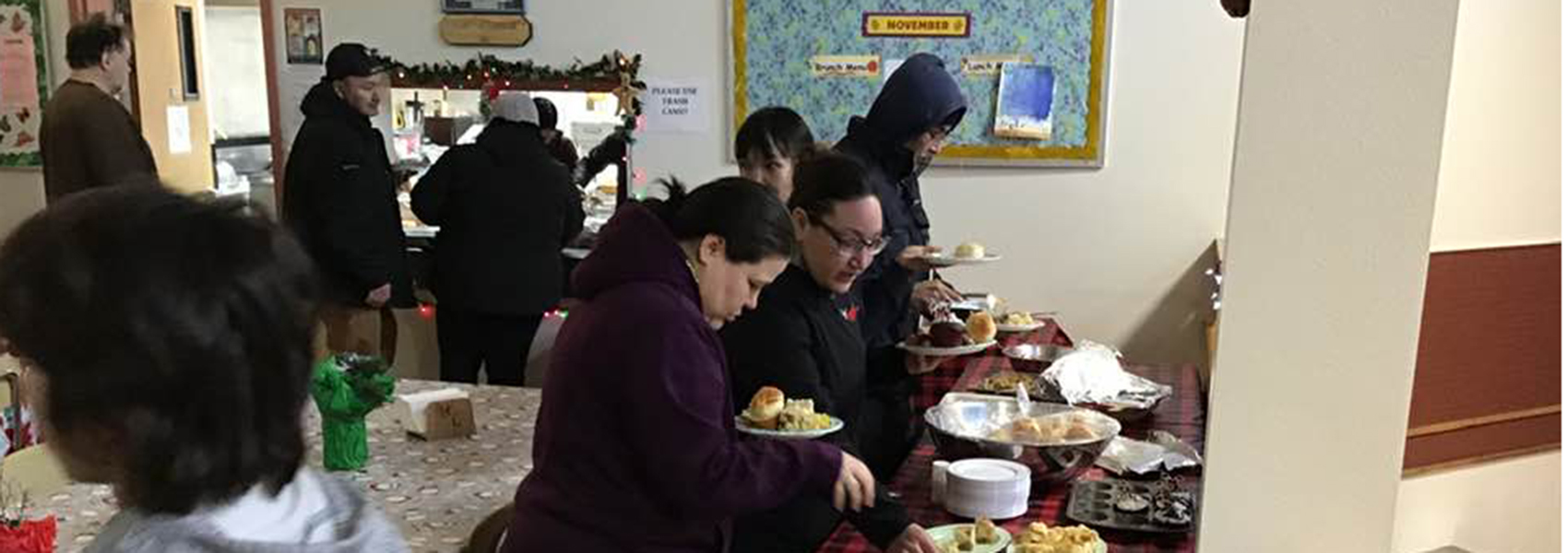 Students and members of the community have a Christmas potluck.